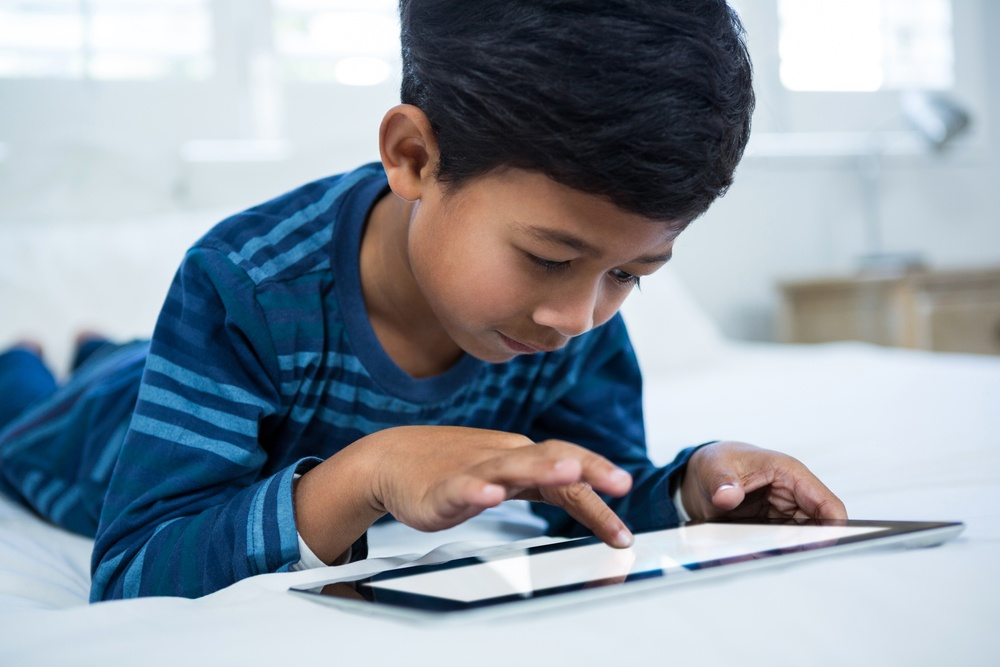 Boy using digital tablet while relaxing on bed in the bedroom