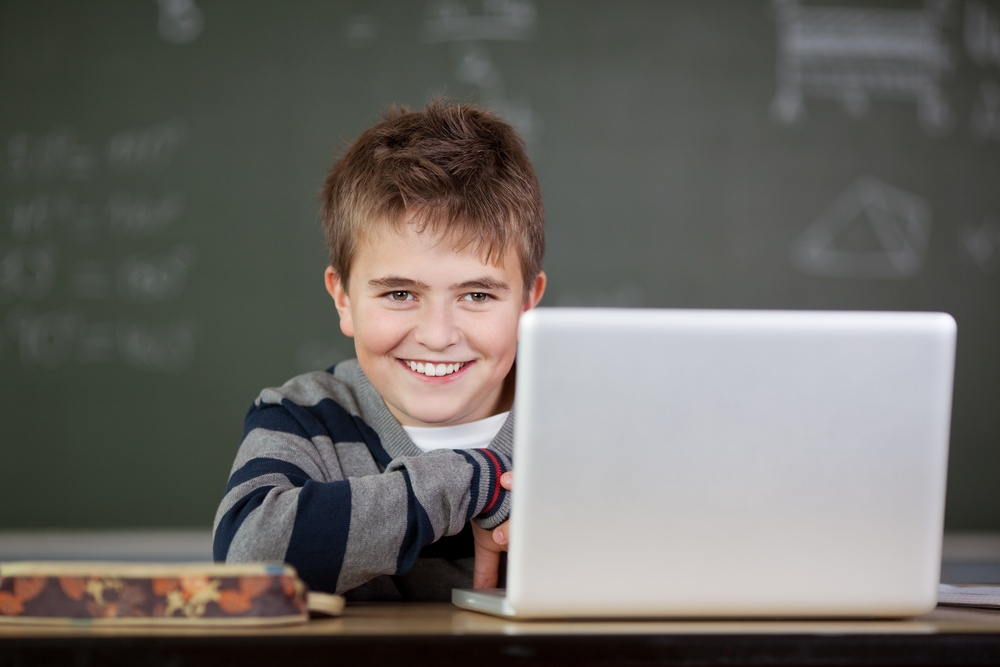 Portrait of male student smiling with laptop on desk in classroom