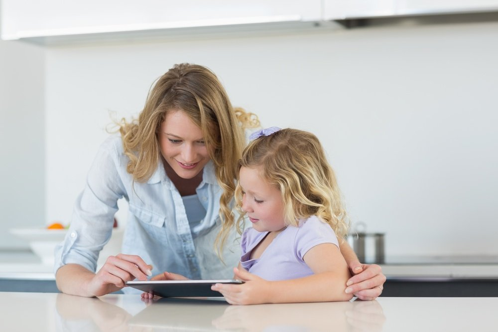 Woman and daughter using tablet computer together at table in kitchen