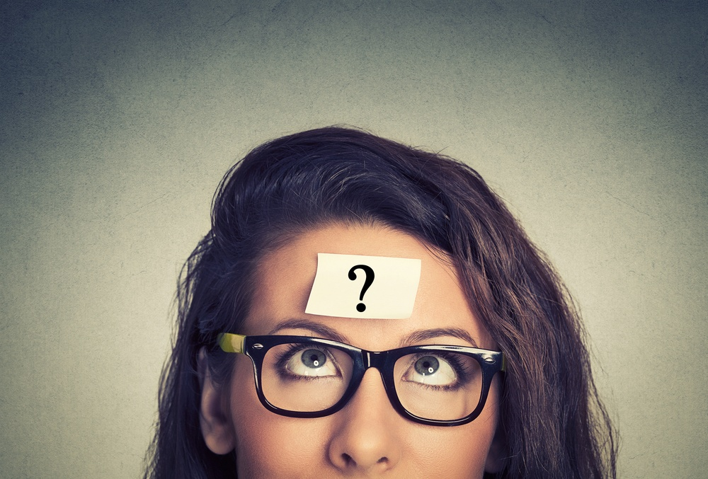 thinking woman with question mark on gray wall background